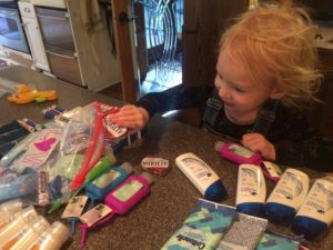 A small helper working to put together love bags for the homeless - conscious life space