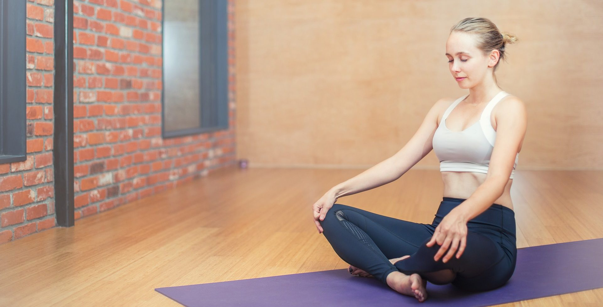 Woman at yoga studio sitting on her mat - Conscious Life Space